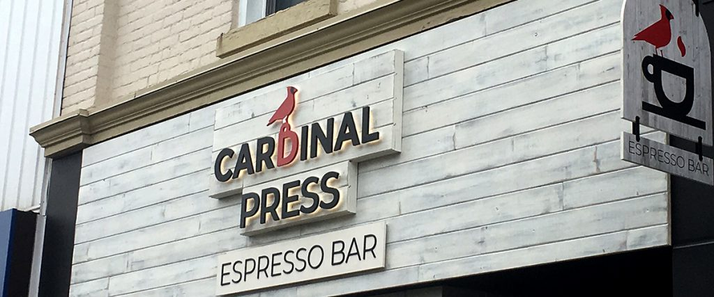 """The sign installation of Cardinal Press's """"espresso bar"""" business sign."""