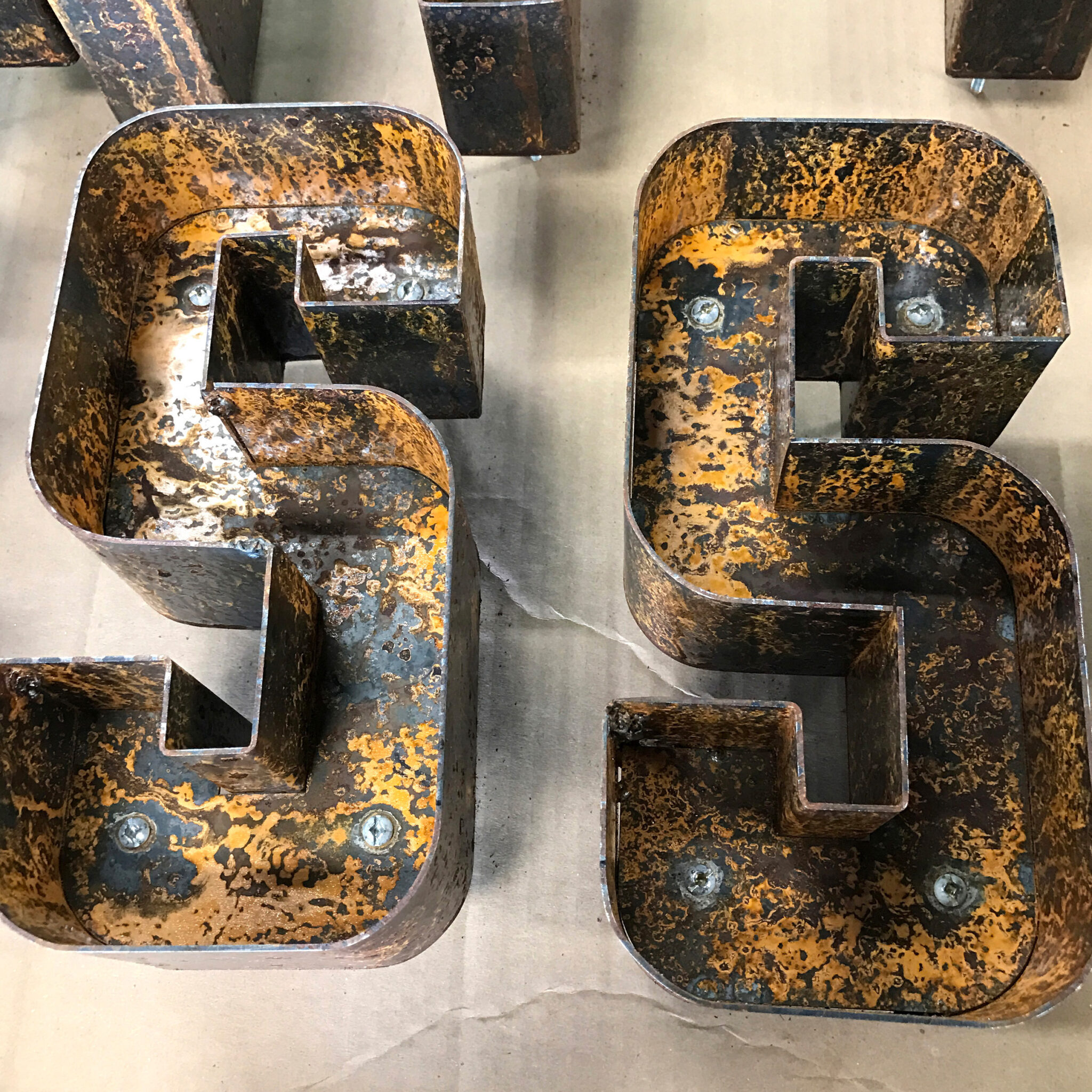 """2 Rusted metal letters that say """"SS""""."""