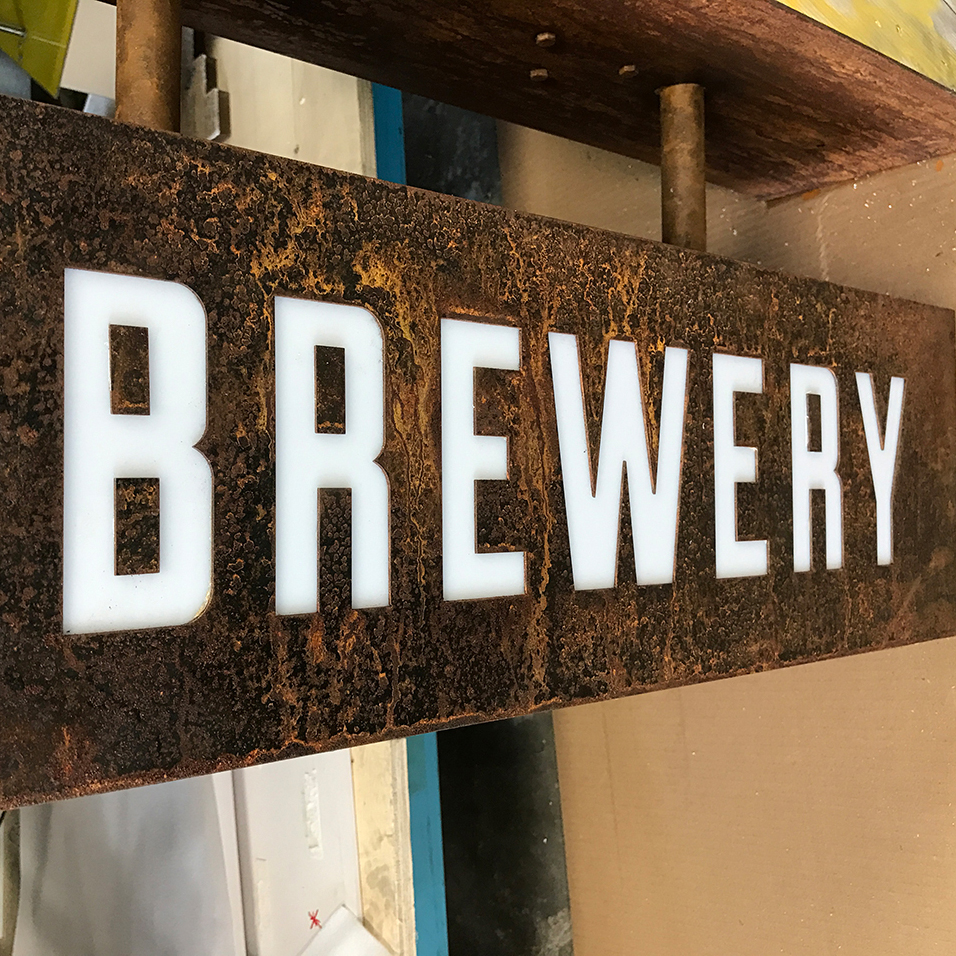 "A sign that is a rustic box style that says ""BREWERY""."