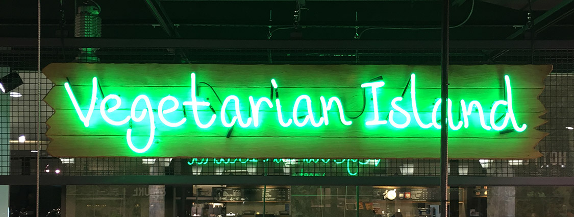 "Glowing in the dark business sign that says ""vegetarian island."""