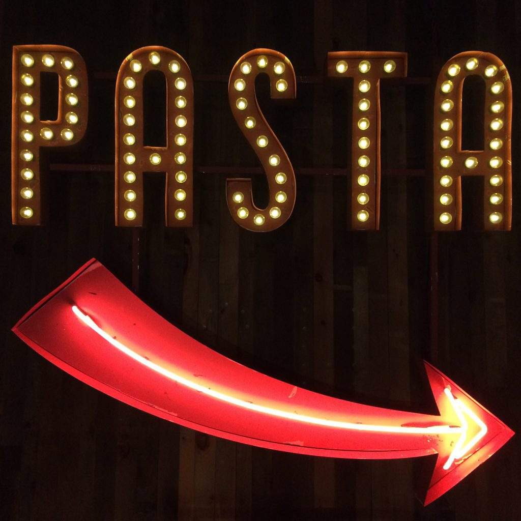 A neon restaurant sign that reads