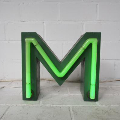 """A neon inlay style letter """"M"""" sign."""