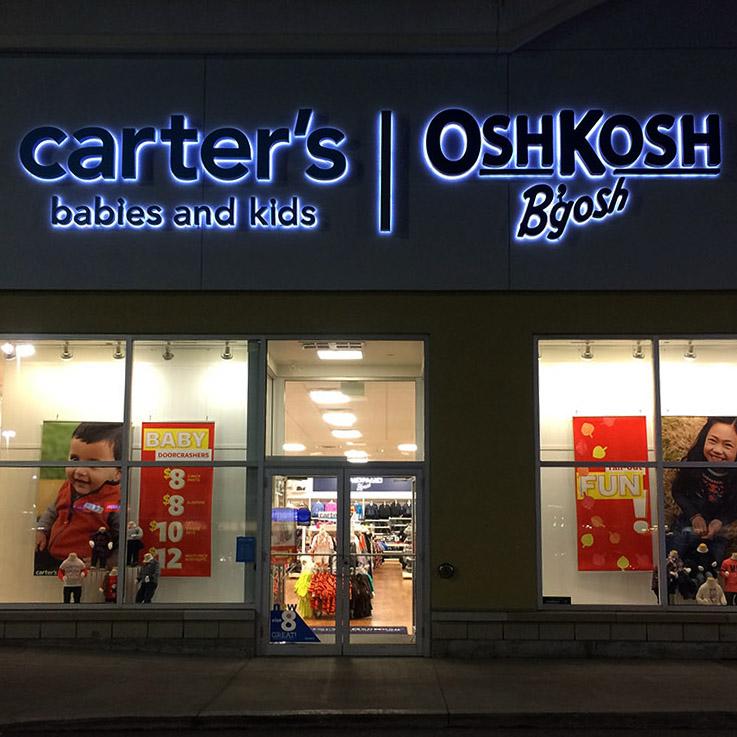 The storefront business sign for Osh Kosh B'gosh.