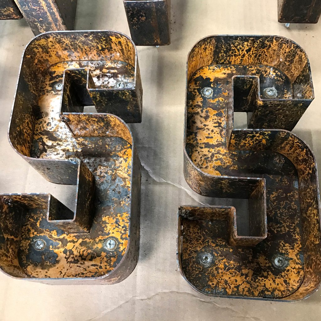 2 Rusted metal letters that say