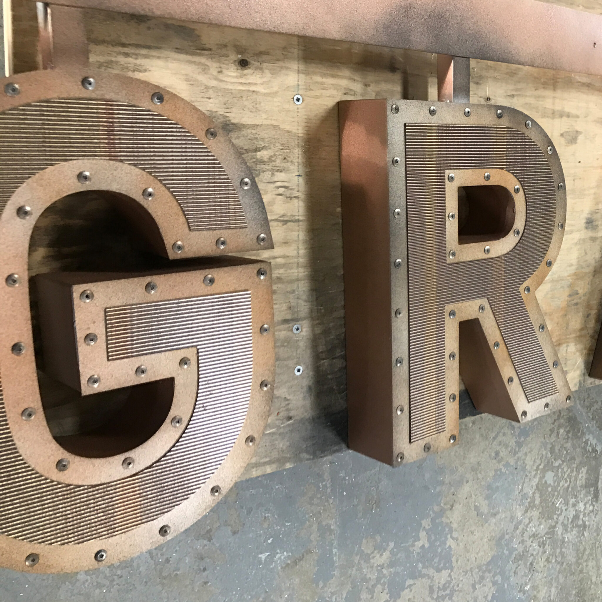 "Studded letters that spell ""GR""."